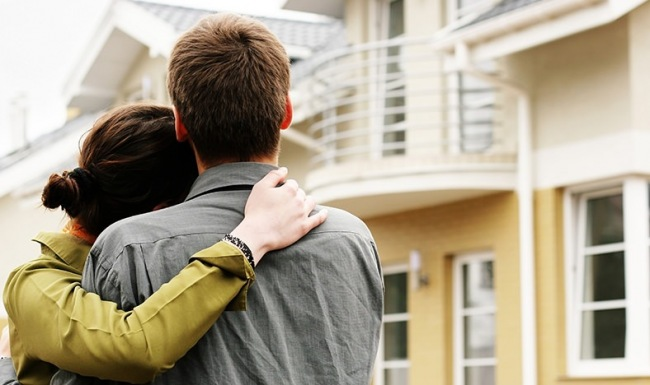 Couple embracing looking at exterior of apartment